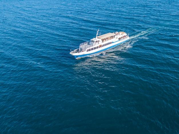 Gli immigrati dei rifugiati nella vista aerea della nave del traghetto nel concetto del mare