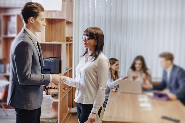 Gli impiegati si stringono la mano nel segno di un accordo sullo sfondo dei loro colleghi