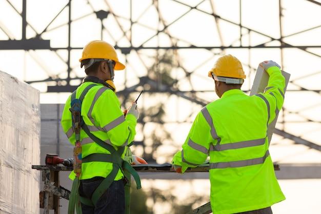 Gli ingegneri asiatici e i consulenti calcolano la quantità di mattoni utilizzati nel contesto della costruzione è la struttura del tetto, concetto di lavoro di squadra di costruzione.