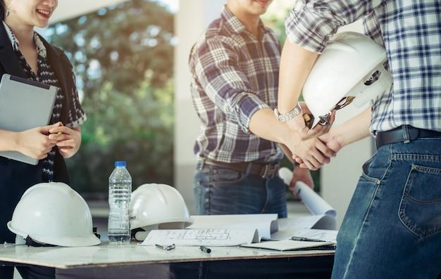 Gli ingegneri si stringono la mano insieme alla segretaria accanto.