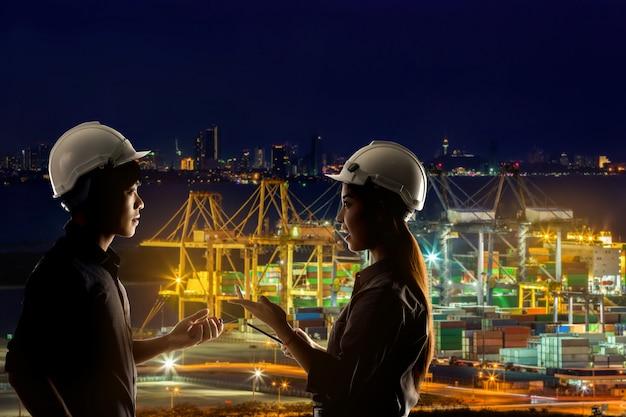 Gli ingegneri stanno lavorando su un porto di spedizione di notte.