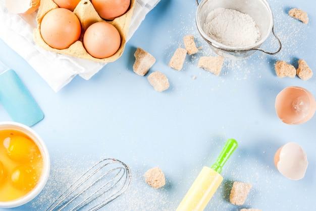 Gli ingredienti e gli utensili per cucinare l'uovo di cottura, la farina, lo zucchero, sbattono, matterello, su fondo blu, vista superiore