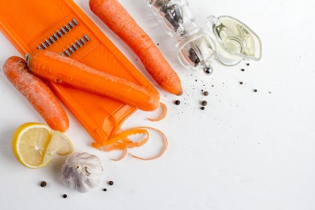 Gli ingredienti per cucinare le carote coreane: carote, burro, peperoncino, coriandolo, limone su un tavolo bianco.