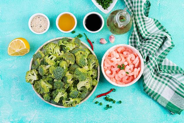 Gli ingredienti per la cottura mescolano il gamberetto con i broccoli si chiudono su una tavola. gamberi e broccoli. vista dall'alto, dall'alto