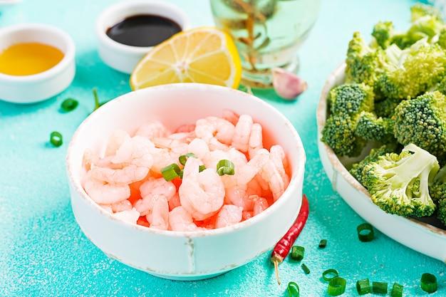 Gli ingredienti per la cottura mescolano il gamberetto con i broccoli si chiudono su una tavola. gamberi e broccoli.