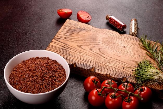 Gli ingredienti per la cucina indiana sono su una superficie nera. la composizione del piatto comprende riso integrale, erbe e spezie.