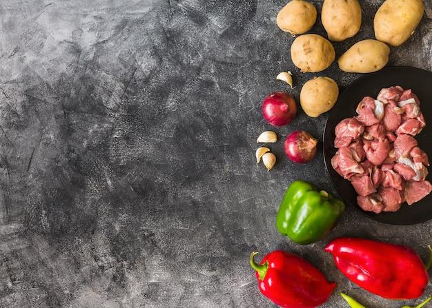 Gli ingredienti per la fabbricazione della carne cruda sul fondo della carta da parati di lerciume strutturano