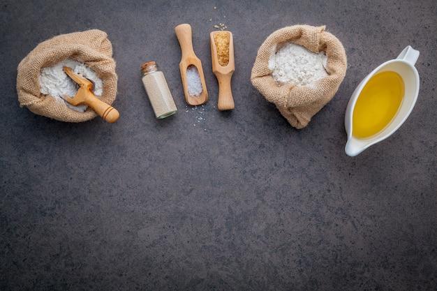 Gli ingredienti per la pasta della pizza fatta in casa su sfondo scuro di pietra.