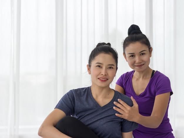 Gli insegnanti di yoga asiatici insegnano agli studenti uno contro uno in palestra a essere sani e forti.