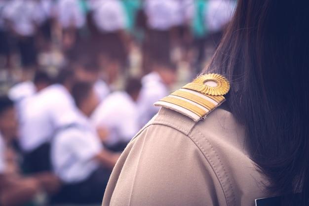 Gli insegnanti tailandesi asiatici in uniforme ufficiale mettono a fuoco sull'accessorio della spalla della banda dorata con gli studenti uniformi