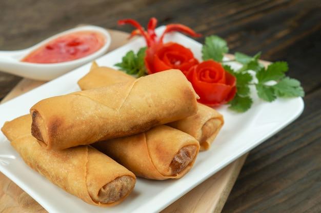 Gli involtini primavera fritti cinesi sono serviti con salsa di peperoncino e pomodori rosa decorati con foglie verdi su legno, spazio. concetto di cibo asiatico