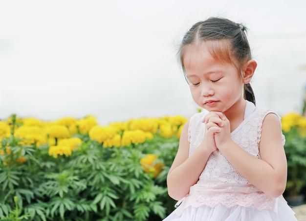 Gli occhi vicini piccola ragazza asiatica che prega al giardino.