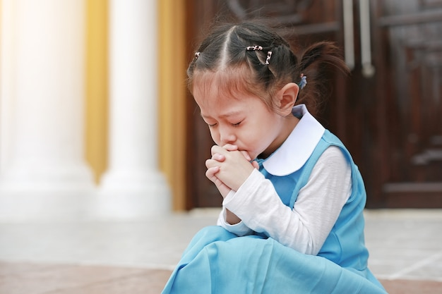 Gli occhi vicini piccola ragazza asiatica del bambino nella preghiera dell'uniforme dello studente. spiritualità e religione.
