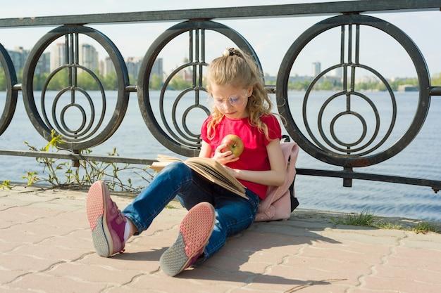 Gli occhiali d'uso della ragazza del bambino con lo zaino sta leggendo il libro