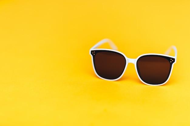 Gli occhiali da sole bianchi su fondo giallo luminoso, copyspace, l'estate sta venendo il concetto
