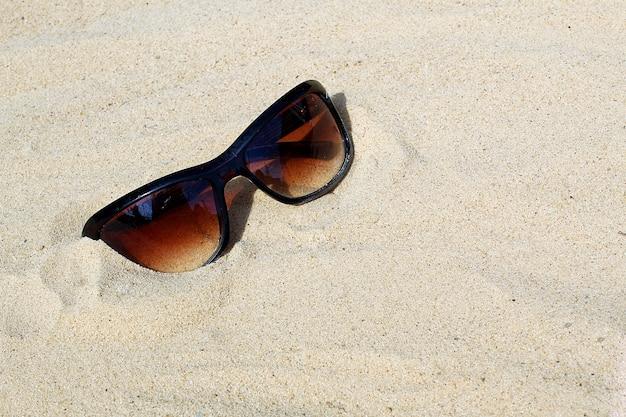 Gli occhiali da sole giacciono sotto il sole cocente.