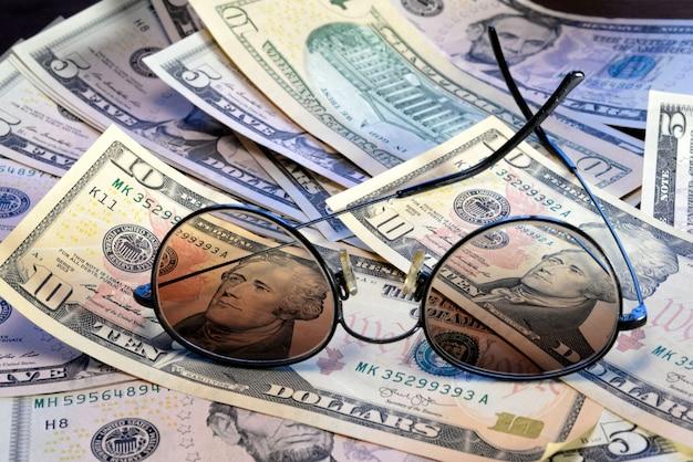 Gli occhiali da sole sono posizionati sulla banconota di dollari americani sparsi in giro