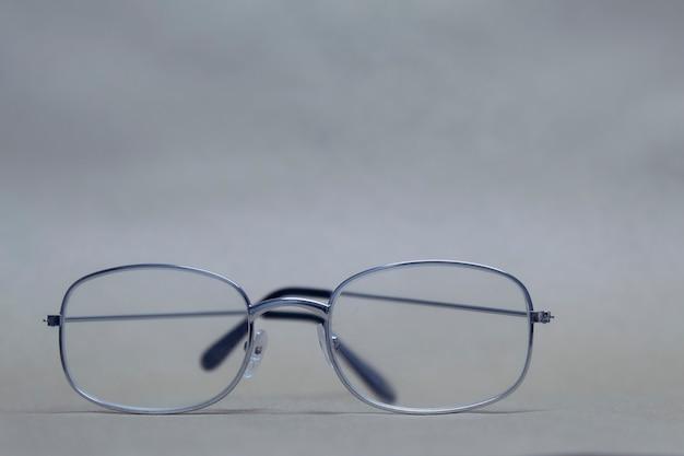 Gli occhiali per la vista con vetro trasparente si trovano su uno sfondo neutro.