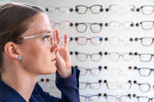 Gli occhiali sono selezionati e testati da una donna in un negozio di ottica. copia spazio