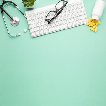 Gli occhiali sulla tastiera senza fili vicino alle pillole hanno rovesciato la bottiglia anteriore e lo stetoscopio sopra superficie verde