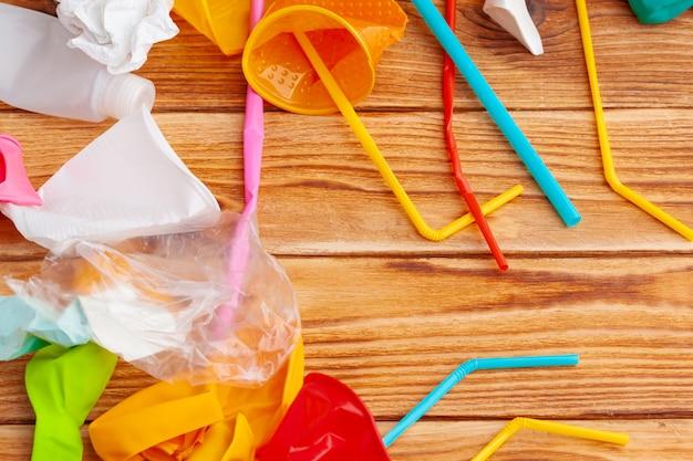 Gli oggetti di plastica, riciclano l'immondizia su una tavola di legno, vista superiore