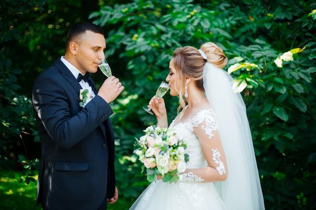 Gli ospiti a un matrimonio con gli sposi tintinnano di bicchieri di champagne o vino bianco