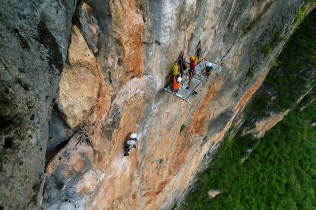 Gli scalatori hanno impostato la tenda per rimanere sul grande muro di roccia. impiccagione estrema su 200 metri