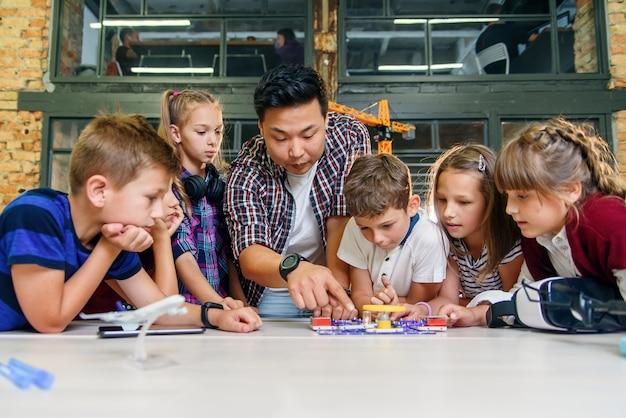 Gli scolari creativi con il giovane insegnante asiatico studiano un costruttore elettronico con il ventilatore e accendono la torcia elettrica.