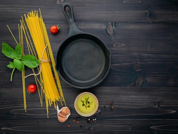 Gli spaghetti sottili sul tavolo di legno nero, piatto disteso.