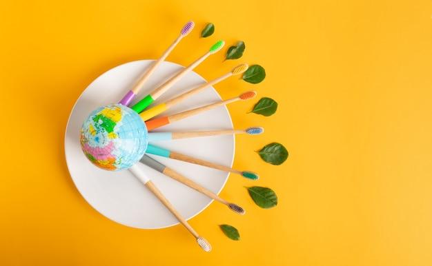 Gli spazzolini di bambù colorati si trovano intorno al piccolo pianeta terra. il concetto di eco che salva il pianeta da plastica, zero sprechi, consapevolezza ambientale