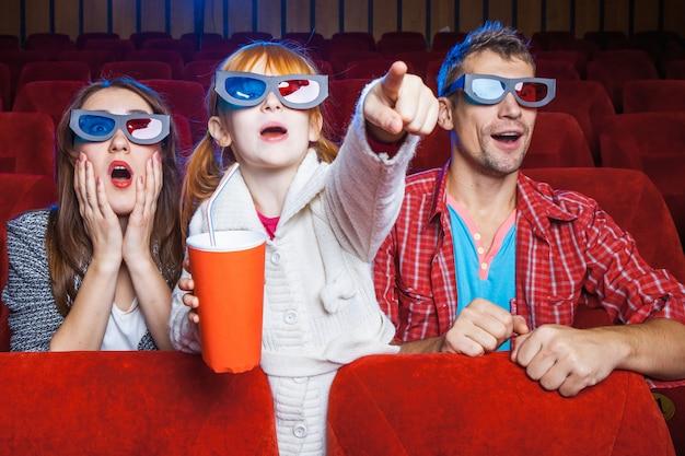 Gli spettatori seduti al cinema e guardare film con tazze di cola.