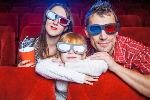 Gli spettatori seduti al cinema e guardare film con una tazza di cola.