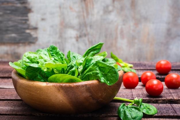 Gli spinaci freschi del bambino lasciano in una ciotola e nei pomodori ciliegia su una tavola di legno
