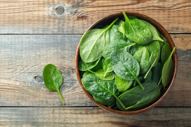 Gli spinaci freschi va in ciotola sulla tavola di legno.
