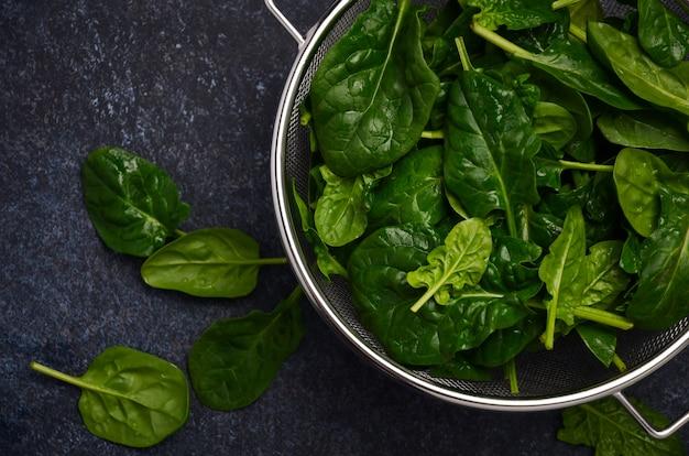 Gli spinaci verdi freschi va su un fondo concreto scuro