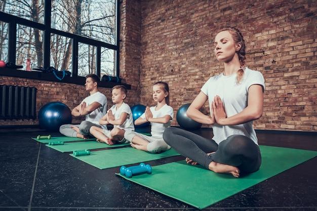 Gli sportivi che fanno yoga sul pavimento.