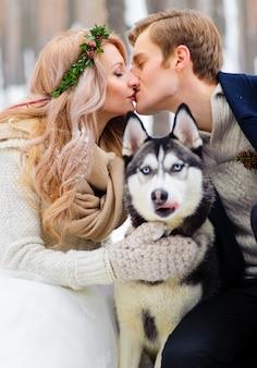 Gli sposi allegri camminano sul sentiero nella foresta nevosa con due cani siberiani.