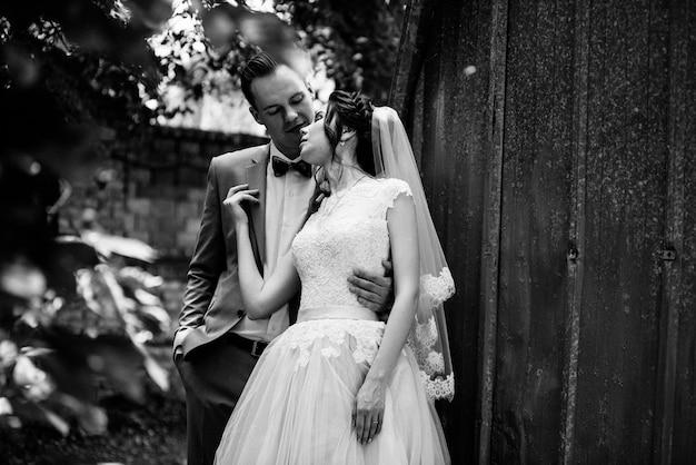Gli sposi camminano nel giardino sullo sfondo di una ghirlanda di lampadine e porte di metallo. foto in bianco e nero