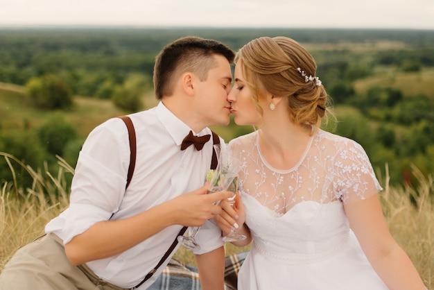 Gli sposi hanno fatto un picnic in natura. amorevole sposa e lo sposo baciano e bevono champagne seduti su un copriletto e si guardano dopo la cerimonia nuziale.