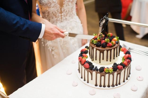 Gli sposi hanno tagliato la torta nuziale al cioccolato.