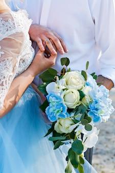 Gli sposi indossano anelli. cerimonia matrimoniale. il bouquet della sposa sposa e sposo con anelli.