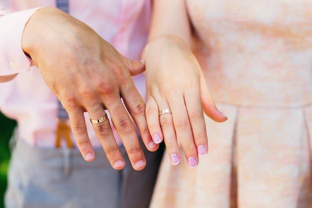 Gli sposi mostrano le loro mani con fedi nuziali sulle dita
