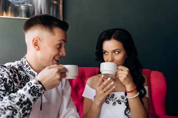 Gli sposi novelli allegri riposano su un sofà rosa luminoso nel caffè