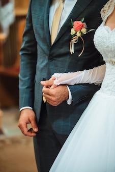 Gli sposi recentemente del primo piano stanno tenendosi la mano a vicenda