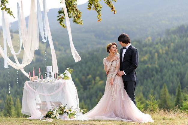 Gli sposi si abbracciano sotto una vecchia quercia. servizio fotografico di matrimonio in montagna. accanto a loro è preparato l'arredamento per la cerimonia.