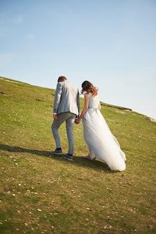 Gli sposi si tengono per mano e corrono in salita su un prato verde. vista posteriore.