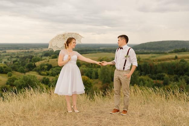 Gli sposi sono in piedi con l'ombrello contro il bellissimo paesaggio