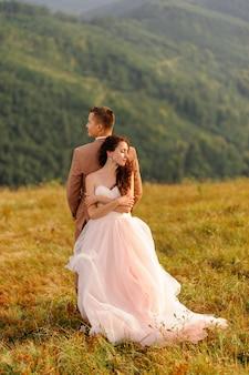 Gli sposi sono in piedi con le spalle l'un l'altro. tramonto. foto di matrimonio su uno sfondo di montagne autunnali. un forte vento gonfia i capelli e il vestito.