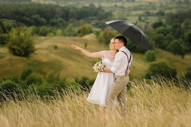 Gli sposi sono in piedi contro il bellissimo paesaggio con un ombrello.