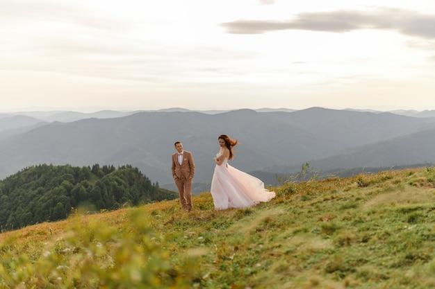 Gli sposi sono vicini l'uno all'altro sullo sfondo delle montagne autunnali. lo sposo ammira sua moglie.